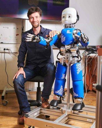 Dr. Matěj Hoffmann, vedoucí skupiny humanoidní robotiky na katedře kybernetiky FEL ČVUT s robotem iCub
